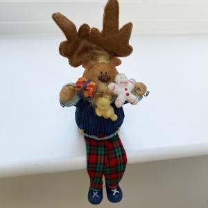 Shelf-sitting reindeer holding toys